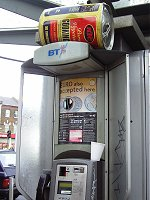 A large can of oil on top of a public phone.